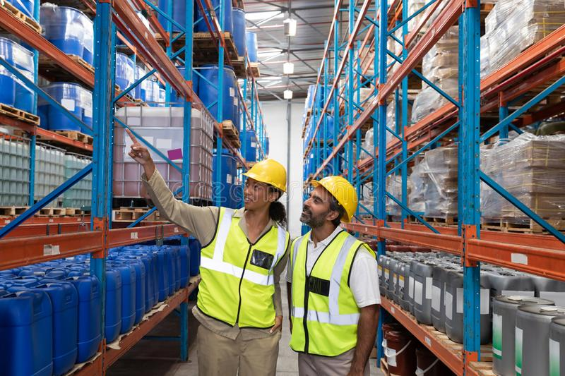 Female worker showing something to male worker in warehouse. Front view of female worker showing something to male worker in warehouse. This is a freight royalty free stock images
