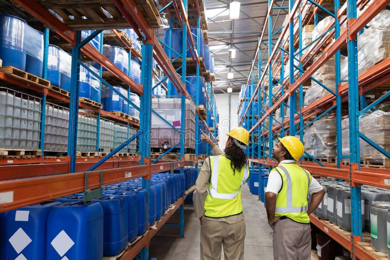 Female worker showing something to male worker in warehouse. Rear view of female worker showing something to male worker in warehouse. This is a freight royalty free stock image