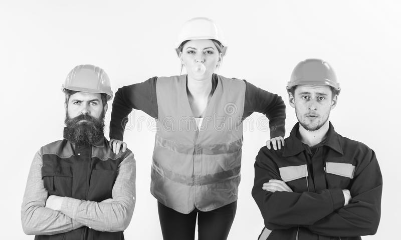 Female worker supported by men in uniform, put hands on male shoulders. Men and woman in helmets with confident faces stock photography