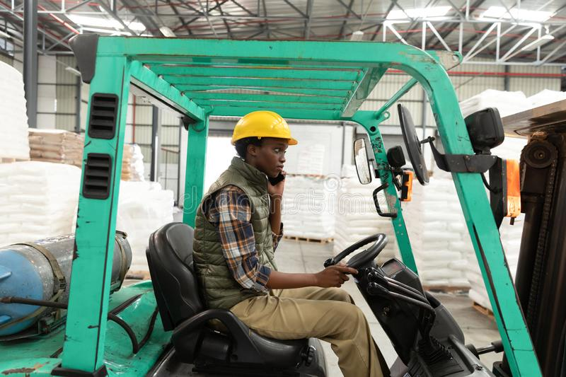 Female worker talking on mobile phone while driving forklift in warehouse. Side view of female worker talking on mobile phone while driving forklift in warehouse royalty free stock photos