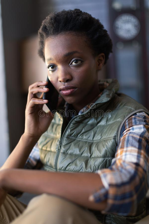 Female worker talking on mobile phone in warehouse. Close-up of African-american female worker talking on mobile phone in warehouse. This is a freight royalty free stock photography