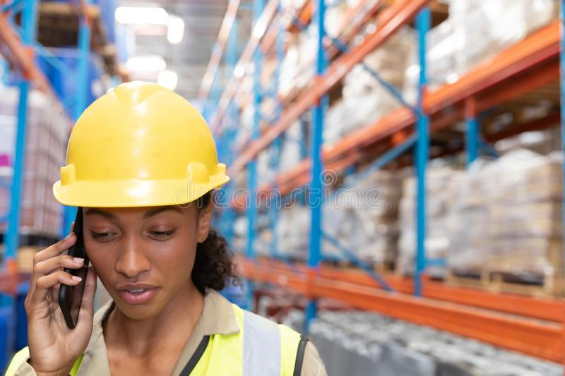 Female worker talking on mobile phone in warehouse. Close-up of female worker talking on mobile phone in warehouse. This is a freight transportation and stock photo