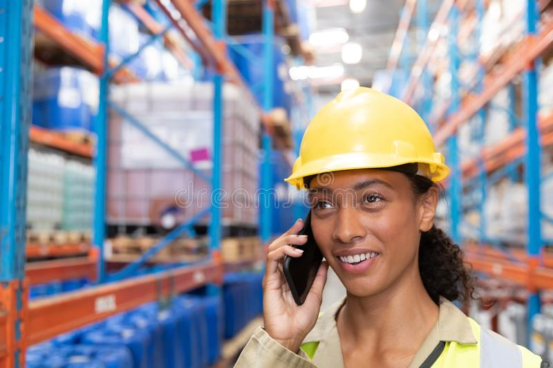 Female worker talking on mobile phone in warehouse. Close-up of female worker talking on mobile phone in warehouse. This is a freight transportation and royalty free stock photo