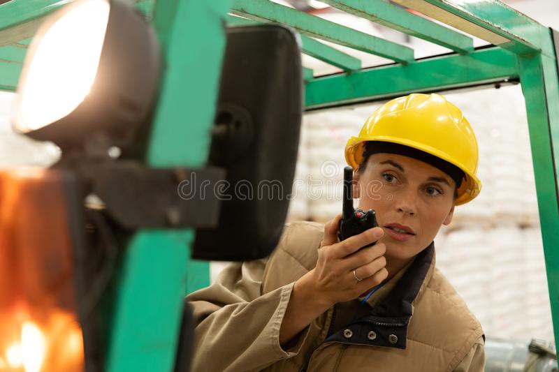 Female worker talking on walkie-talkie while driving forklift in warehouse. Close-up of female worker talking on walkie-talkie while driving forklift in royalty free stock photography