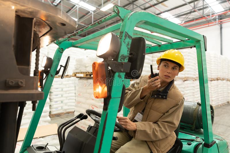 Female worker talking on walkie-talkie while driving forklift in warehouse. Front view of female worker talking on walkie-talkie while driving forklift in stock photos