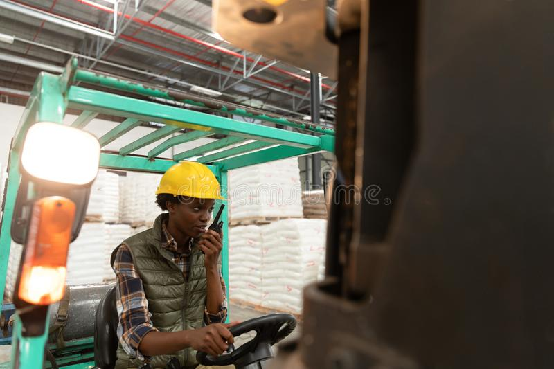 Female worker talking on walkie-talkie while driving forklift in warehouse. Front view of female worker talking on walkie-talkie while driving forklift in royalty free stock image