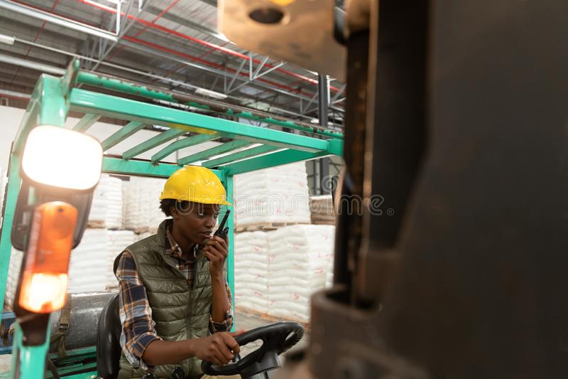 Female worker talking on walkie-talkie while driving forklift in warehouse. Front view of female worker talking on walkie-talkie while driving forklift in stock photography