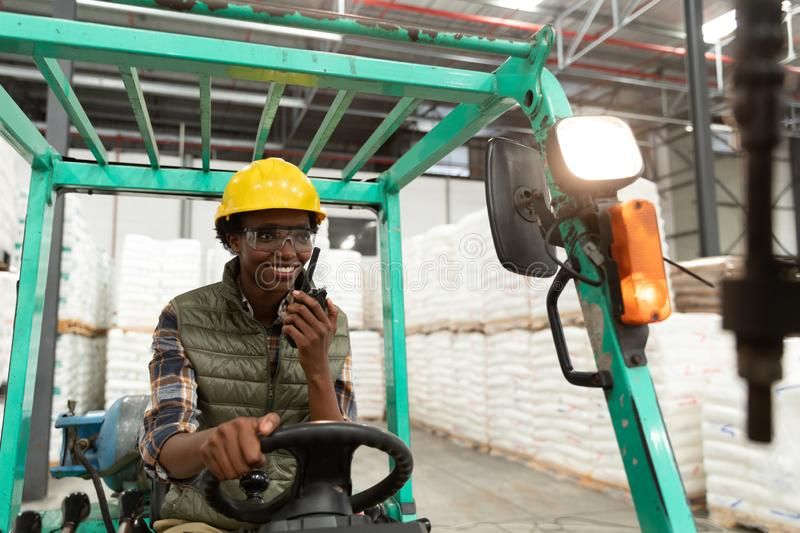Female worker talking on walkie-talkie while driving forklift in warehouse. Happy female worker talking on walkie-talkie while driving forklift in warehouse stock images