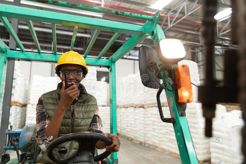 Female worker talking on walkie-talkie while driving forklift in warehouse. Happy female worker talking on walkie-talkie while driving forklift in warehouse royalty free stock photos