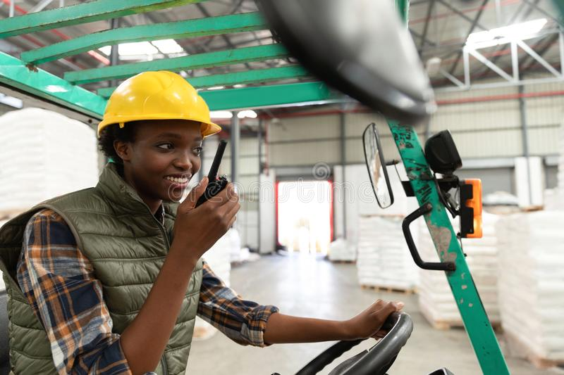 Female worker talking on walkie-talkie while driving forklift in warehouse. Happy female worker talking on walkie-talkie while driving forklift in warehouse stock image
