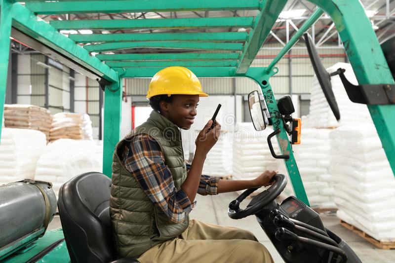 Female worker talking on walkie-talkie while driving forklift in warehouse. Side view of female worker talking on walkie-talkie while driving forklift in stock image
