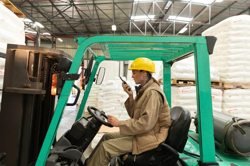 Female worker talking on walkie-talkie while driving forklift in warehouse. Side view of female worker talking on walkie-talkie while driving forklift in stock photos