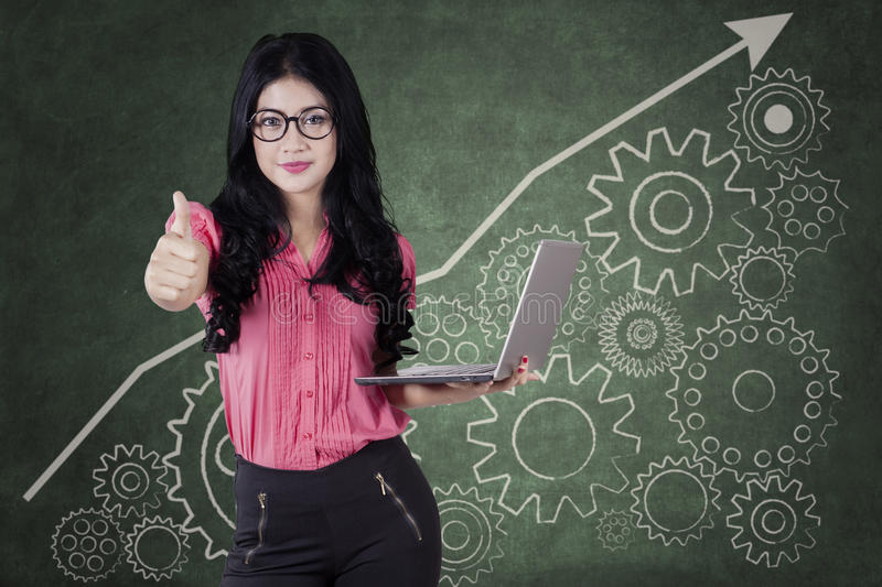 Female worker with thumb up and gears. Young businesswoman showing thumb up while holding a laptop computer with business graph and gear background stock photo