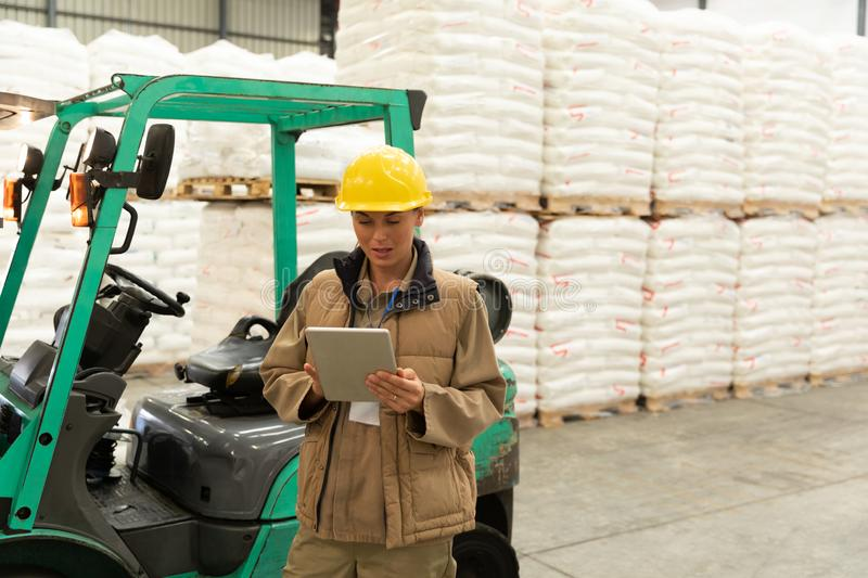 Female worker using digital tablet in warehouse. Front view of female worker using digital tablet in warehouse. This is a freight transportation and distribution royalty free stock image