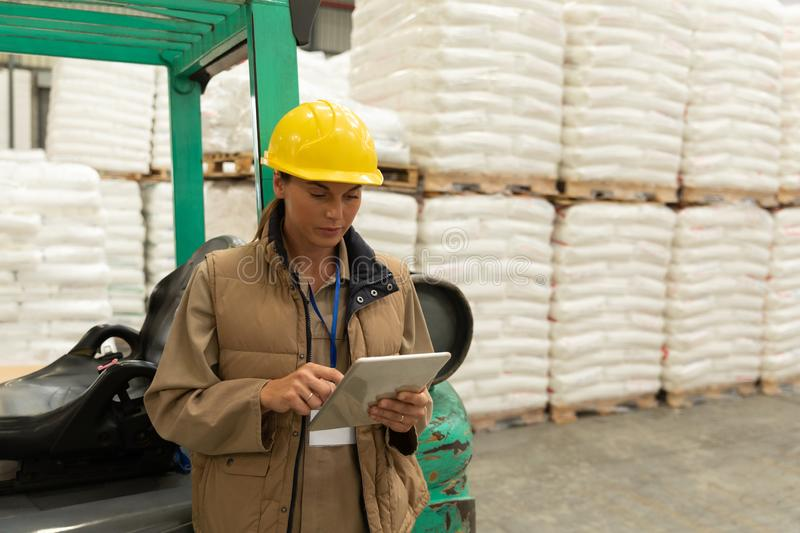 Female worker using digital tablet in warehouse. Front view of female worker using digital tablet in warehouse. This is a freight transportation and distribution royalty free stock images