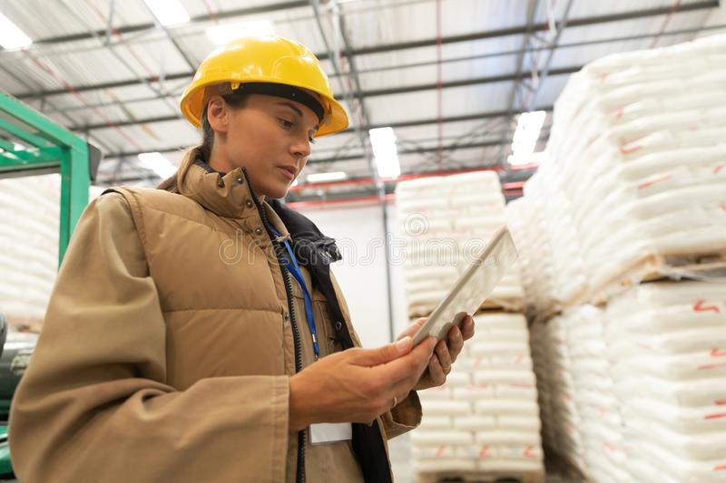 Female worker using digital tablet in warehouse. Low angle view of female worker using digital tablet in warehouse. This is a freight transportation and royalty free stock photos