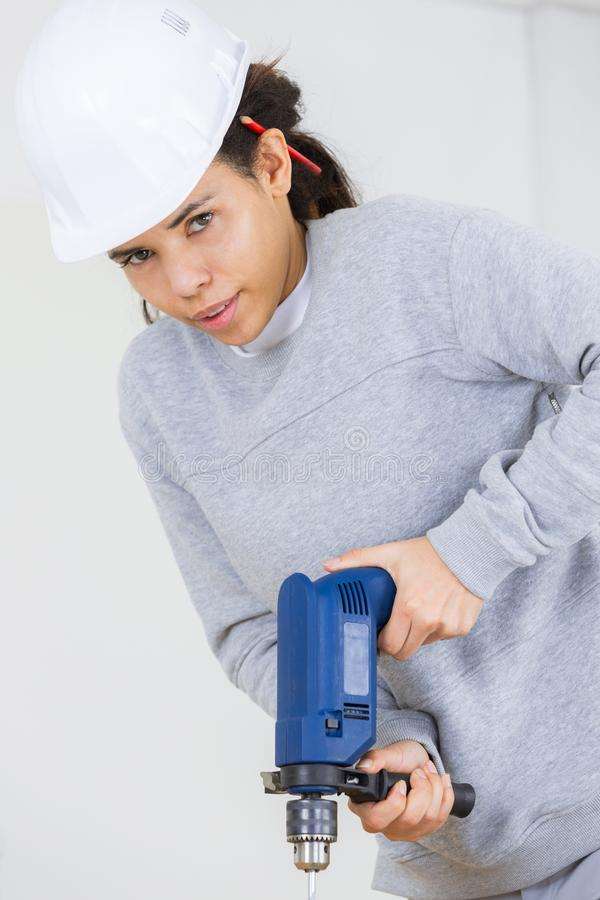 Female worker using power tool to drill royalty free stock image