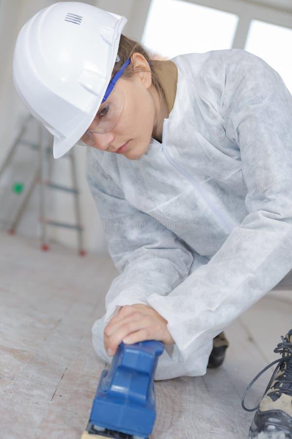Female worker using sander on floor stock photo