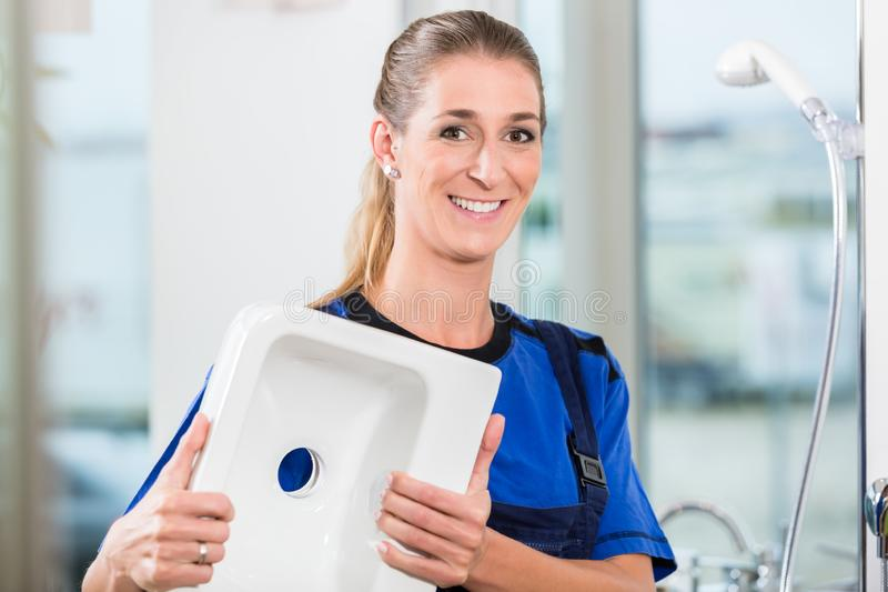 Female worker at work in a sanitary shop with high-quality ceramic fixtures royalty free stock photography