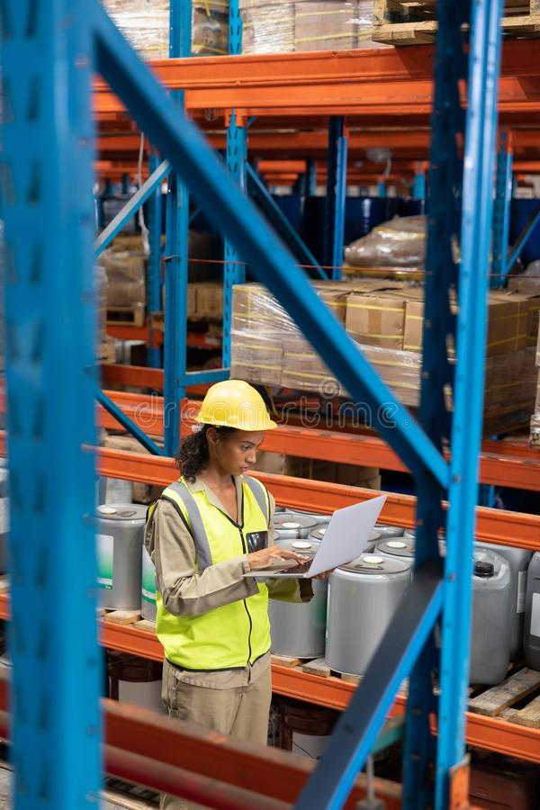 Female worker working on laptop in warehouse. Side view of female worker working on laptop in warehouse. This is a freight transportation and distribution royalty free stock photo