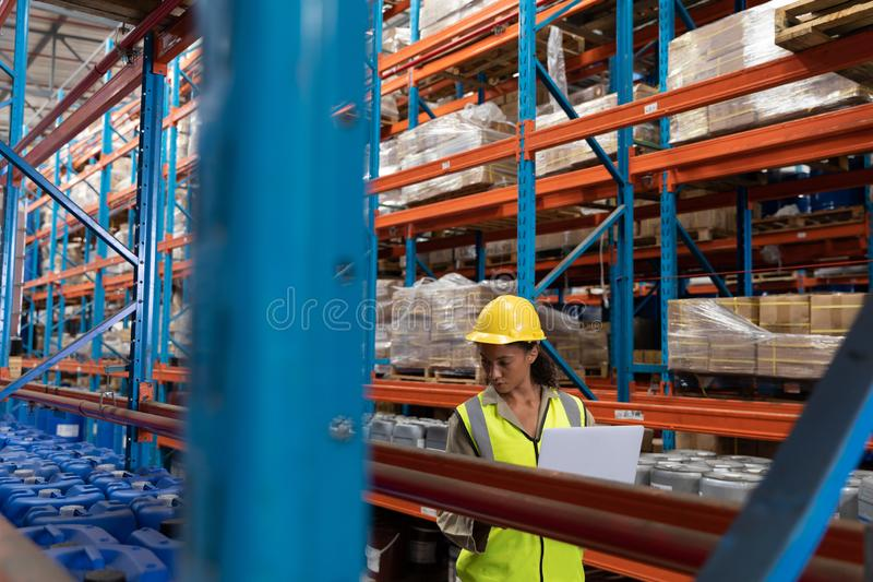 Female worker working in warehouse. Front view of female worker working in warehouse. This is a freight transportation and distribution warehouse. Industrial and royalty free stock image