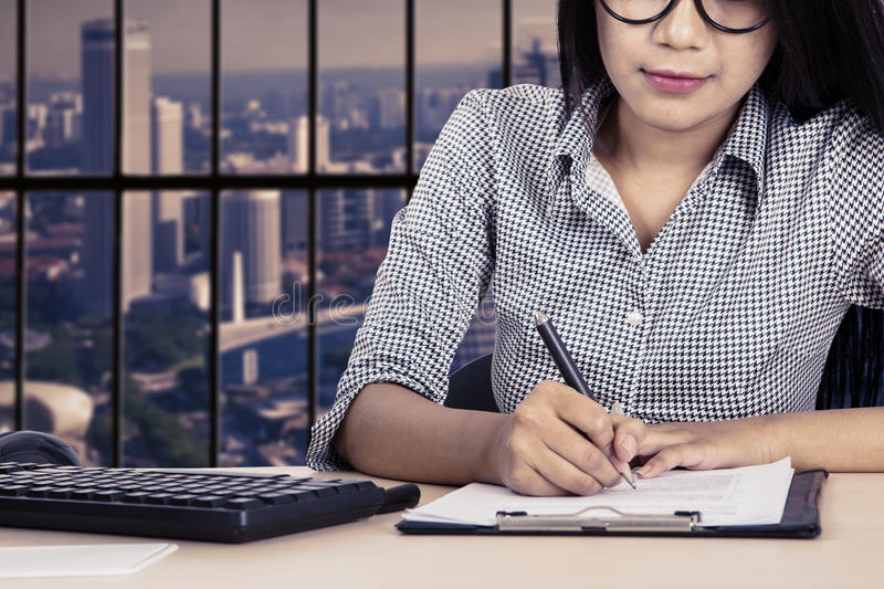 Female worker writes on paperwork stock photography