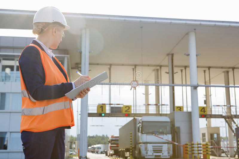 Female worker writing on clipboard while looking at trucks entering in shipping yard stock photos