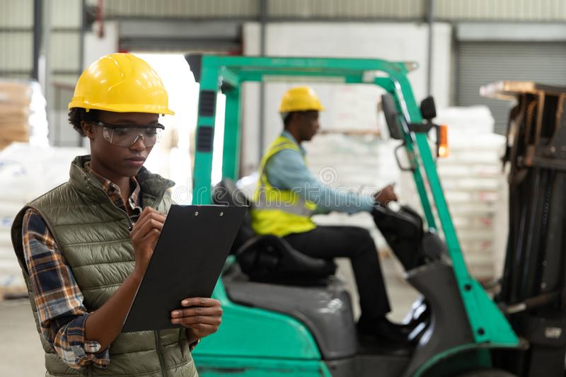 Female worker writing on clipboard in warehouse. Front view of female worker writing on clipboard in warehouse. This is a freight transportation and distribution stock photo