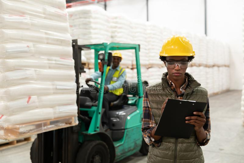 Female worker writing on clipboard in warehouse. Front view of female worker writing on clipboard in warehouse. This is a freight transportation and distribution royalty free stock photography