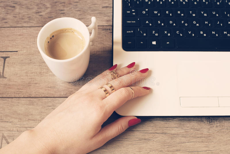 Female working on laptop in a cafe. White mug of coffee. Close up of a woman hand with rings and long nails, painted in red. Female working on laptop in a cafe stock photo