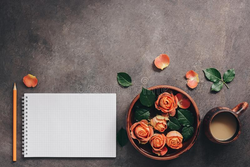 Female workspace with blank notepad, cup of coffee,ceramic bowl with flowers of coral roses and pencil. Top view, flat lay royalty free stock image