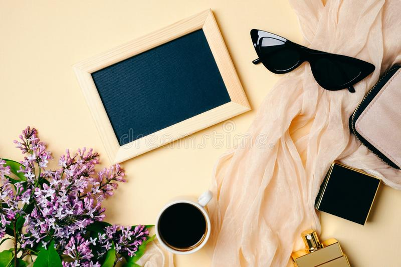 Female workspace with photo frame, sunglasses, silk scarf, coffee cup, accessories, perfume bottle, lilac flowers on beige stock photos