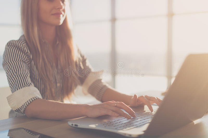 Female writer typing using laptop keyboard at her workplace in the morning. Woman writing blogs online, side view close royalty free stock image