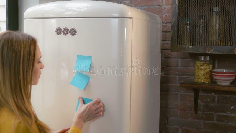 Female writes note on fridge. royalty free stock images