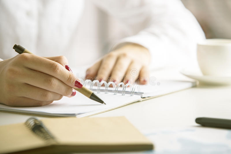 Female writing in notepad. Female writing in spiral notepad placed on desktop with other items. Close up stock images