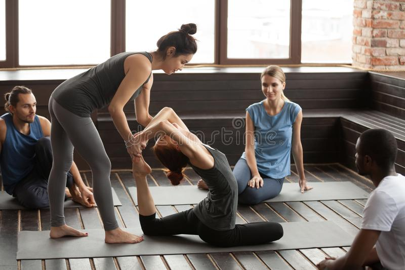 Female yoga instructor helping woman doing exercise at group tra. Female yoga instructor helping women developing flexibility doing exercise at multi-ethnic royalty free stock images
