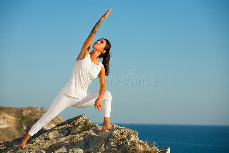 Female yoga model working out training on the top of mountain on background of sea. stock image