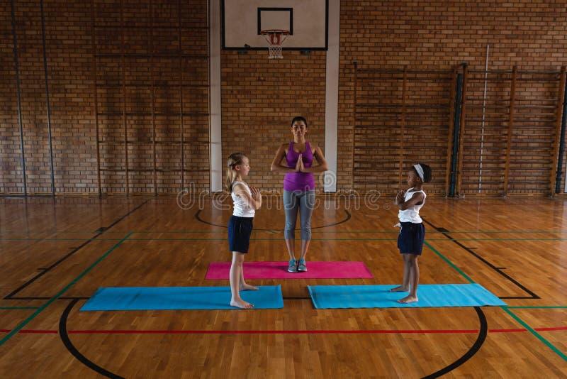 Female yoga teacher teaching yoga to school kids in school royalty free stock photos