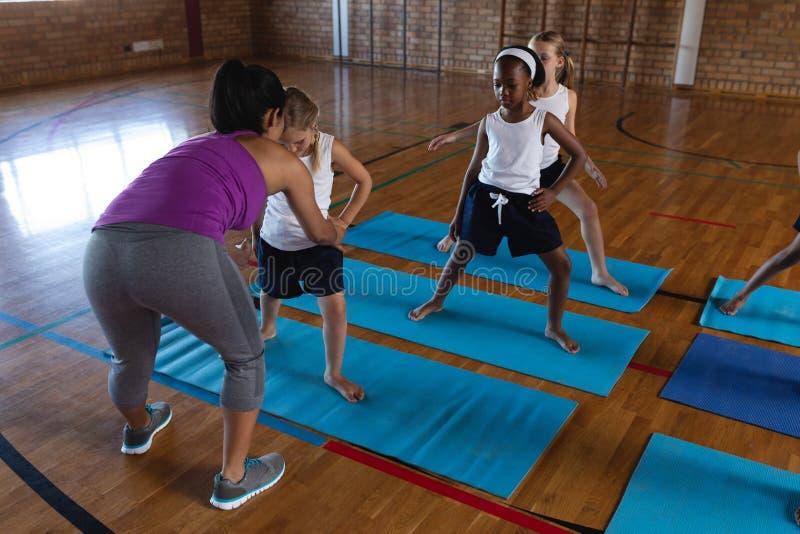 Female yoga teacher teaching yoga to school kids in school stock images