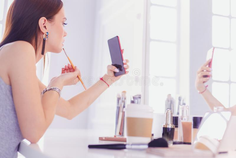 Female young beautiful girl with curly hair and make-up. beautiful woman make self-portrait yourself by phone stock images