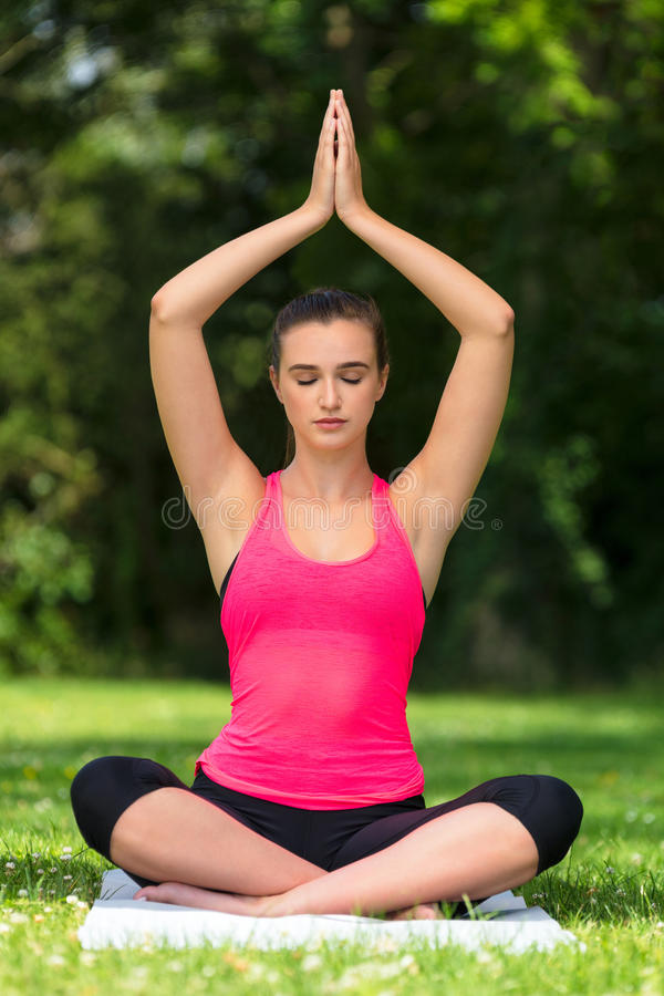 Female Young Fit Healthy Woman or Girl Practicing Yoga Outside. Young fit healthy woman female or girl practicing yoga pose on a mat outside in a natural royalty free stock image