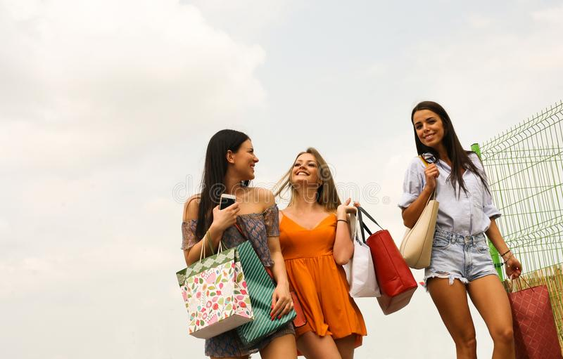 Female young friends doing shopping in the city. stock photo