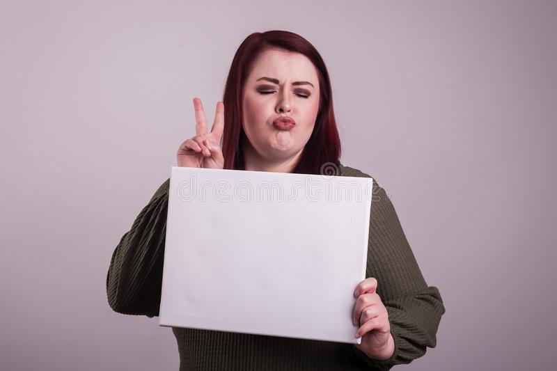 Female young woman holding a blank white sign puckering lips giving a peace sign stock photos