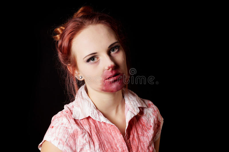 Female zombie with bloody mouth and blouse. On black background stock image