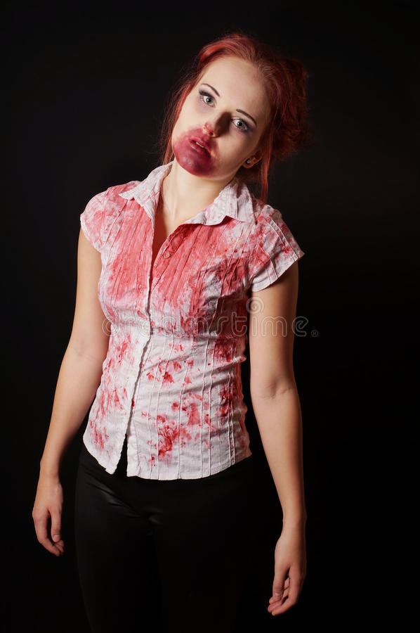 Female zombie with bloody mouth and blouse. On black background royalty free stock photos