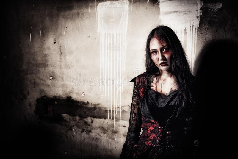 Female zombie corpse standing in front of grunge wall in abandoned house. Horror and Ghost concept. Halloween day festival and. Scary movie theme. Haunted house royalty free stock photos
