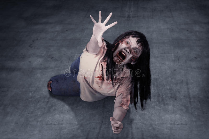 Female zombie crouching on the floor. Halloween concept royalty free stock photo