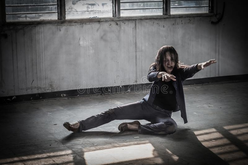 Female zombie crouching on the floor, Halloween concept stock photography