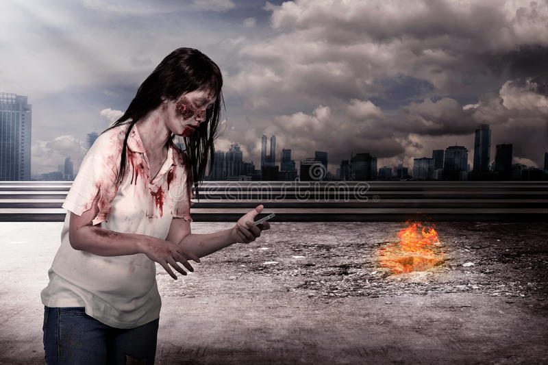 Female zombie holding cellphone. Over burn city background stock photography