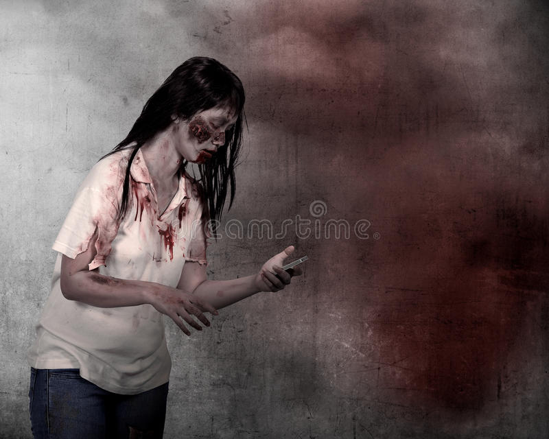 Female zombie holding cellphone. Over grunge background stock photos